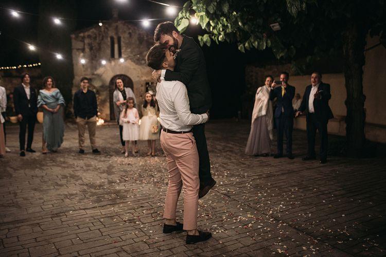 Groom in Pink Wedding Suit Lifting His Groom in a Green Wedding Suit