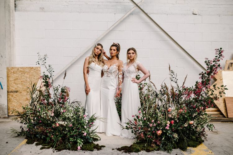 Industrial Wedding Venue with Three Brides Standing by Deep Pink and Foliage Floral Arrangements
