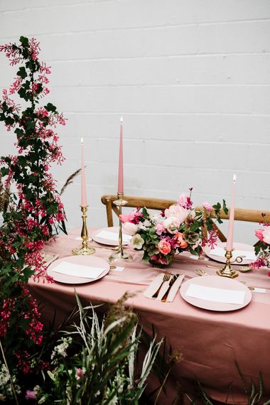 Table Decor with Pink Table Cloth, Pink Tableware, Pink Taper Candles, Gold Cutlery and Deep Pink and Foliage Wedding Flowers