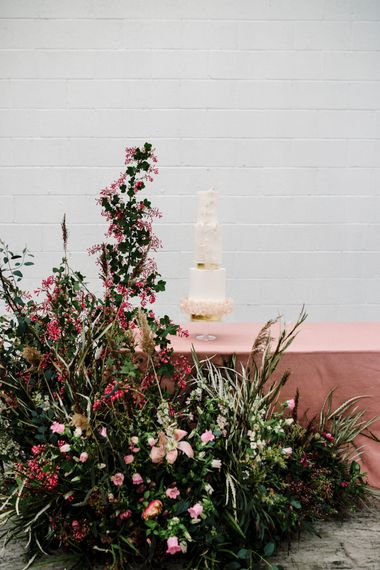 Elegant Wedding Cake with Round and Square Layers Next to Deep Pink and Foliage Floral Arrangement