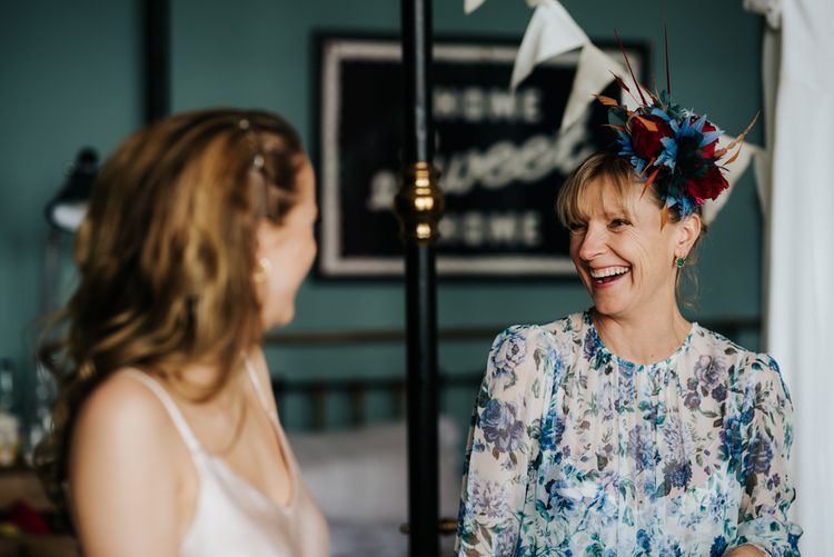 Bride's mother smiles at sister of the bride