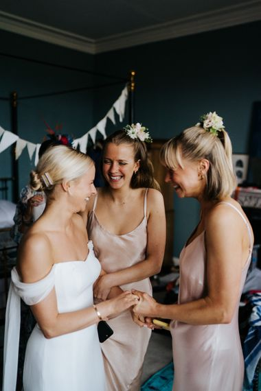 Bride holds hands and smiles at two sister in excited anticipation for the wedding ceremony
