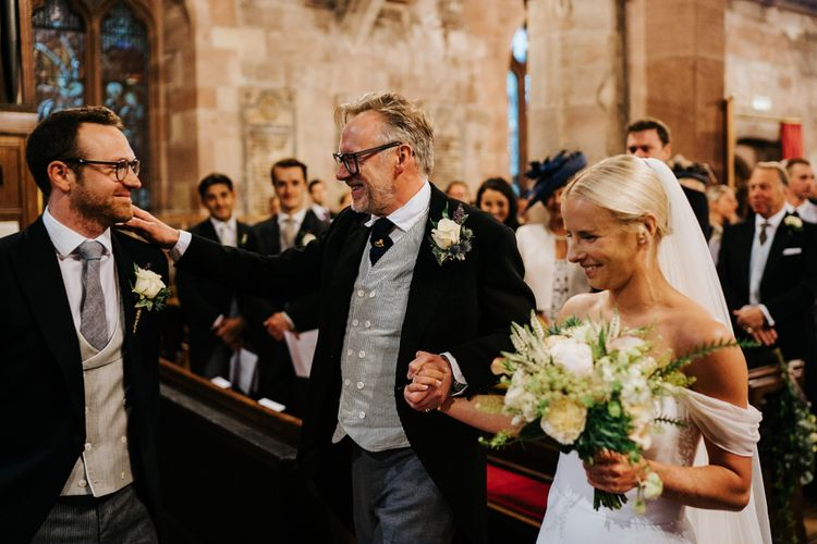 Bride and father of the bride arrive at the front of the aisle and hug the groom