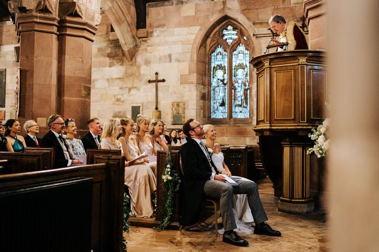 Bride and groom, and bride's family listen attentively to vicar's sermon and smile while doing so