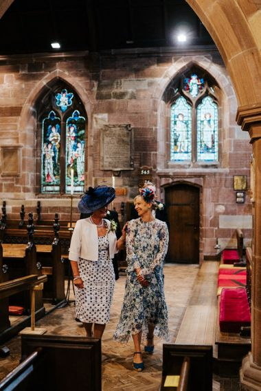 Bride and groom's mother look at each other and exchange a moment of happiness as they walk towards the signing of the register