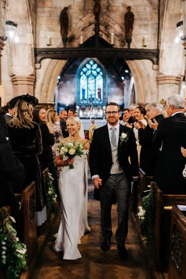 Bride and groom hold hands and walk back down the aisle as husband and wife while smiling at their guests ]