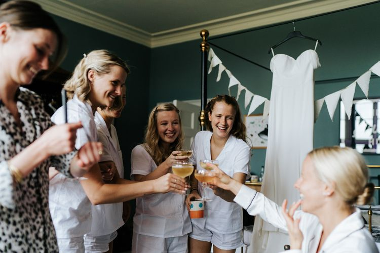 Bride and bridesmaids each hold a glass of champagne and say a toast for the day ahead