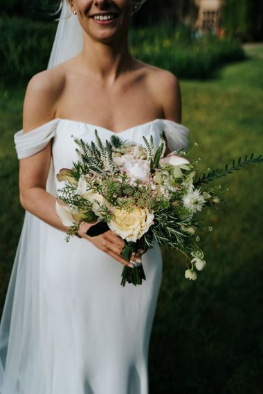 Bride in off the shoulder wedding dress holding a cream rose and foliage wedding bouquet