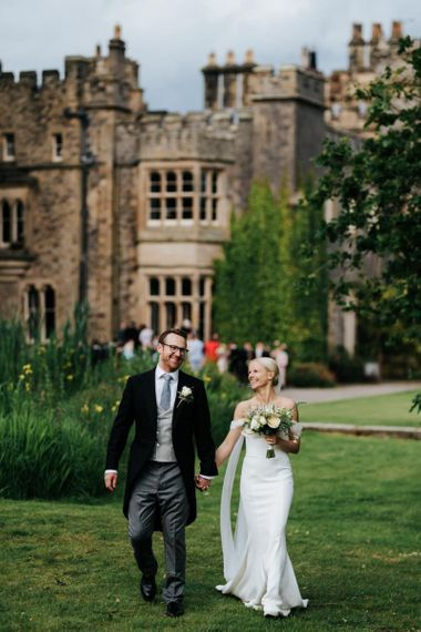Bride and groom walk towards camera with Hawarden Castle in the background