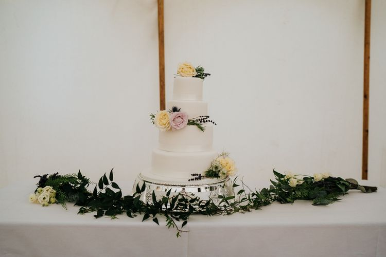 Three-tiered, white wedding cake with yellow and pink roses as decoration