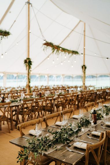 Marquee reception with wooden tables, greenery table runners and hanging festoon lights