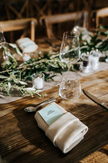 Close-up of placecard and decoration on wooden table to be used for wedding breakfast