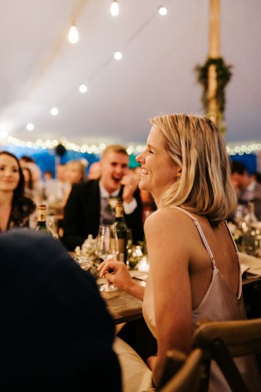 Sister of the bride smiles graciously during groom's speech