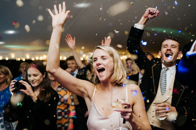 Sister of the bride and guests smiling and cheering as confetti explodes over the dancefloor