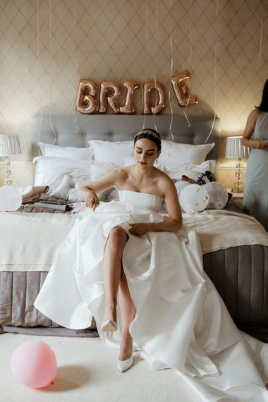 Bride In Strapless Wedding Dress Puts On Shoes With Wedding Balloons
