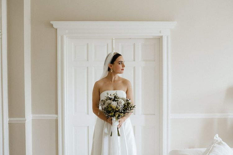 Bride Holds Bouquet In Front Of Strapless Wedding Dress