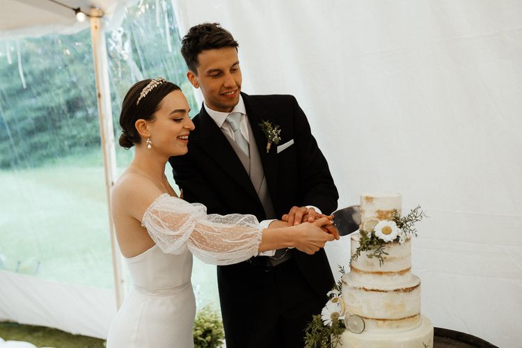 Bride In Strapless Wedding Dress Cuts Cake With Groom