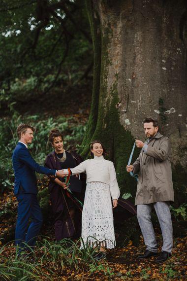 Bride in Crochet Wedding Dress and Woollen Jumper and Groom in Navy Suit Holding Hands During the Wedding Ceremony