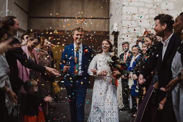 Confetti Moment with Bride in Crochet Wedding Dress and Woollen Jumper and Groom in Navy Suit