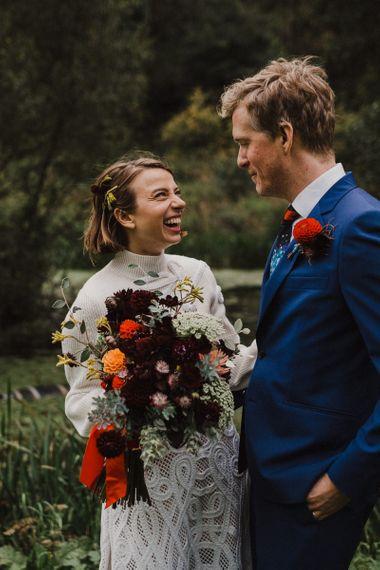 Bride in Crochet Wedding Dress and Woollen Jumper Laughing with Her  Groom in Navy Suit