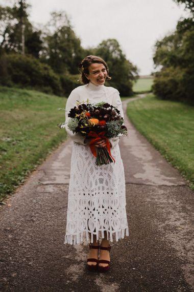 Bride in Crochet Wedding Dress and Woollen Jumper Holding a Orange and Red Dahlia Wedding Bouquet