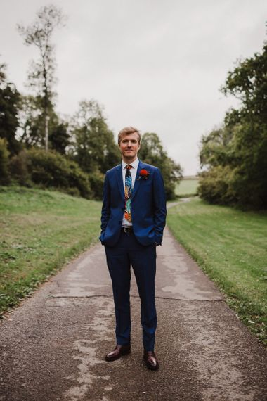 Groom in Navy Paul Smith Suit with Colourful Tie and Dahlia Buttonhole