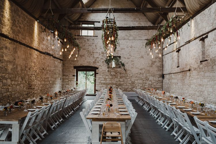 Rustic Reception with, Trestle Tables, Flowers in Bottles and Hanging Edison Bulb Installation