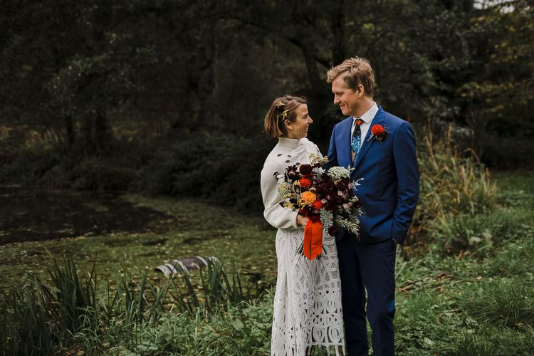 Bride in Crochet Wedding Dress and Woollen Jumper and Groom in Navy Paul Smith Suit Laughing by the Steam
