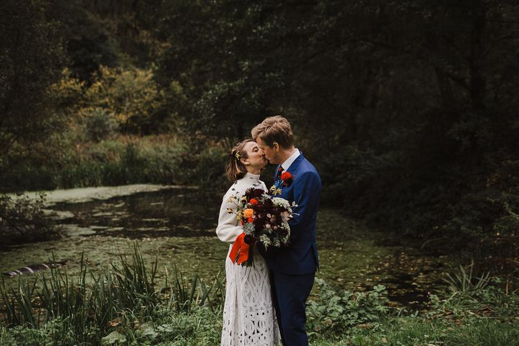 Bride in Crochet Wedding Dress and Woollen Jumper and Groom in Navy Paul Smith Suit Kissing by the Steam