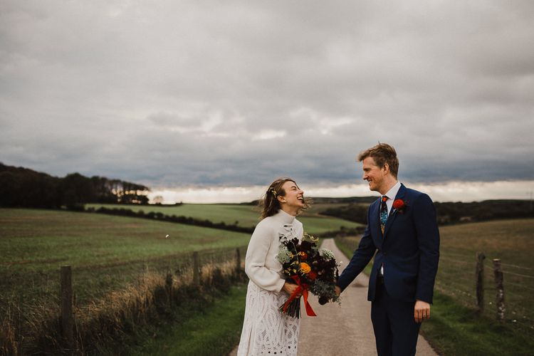 Bride in Crochet Wedding Dress and Woollen Jumper and Groom in Navy Paul Smith Suit Holding Hands on a Country Road