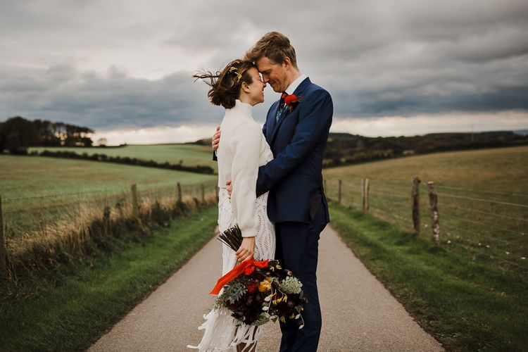 Bride in Crochet Wedding Dress and Woollen Jumper and Groom in Navy Paul Smith Suit Embracing on a Country Road