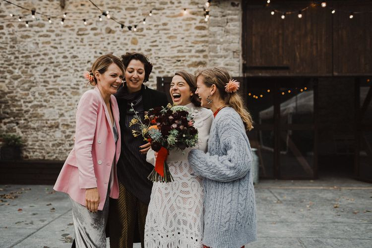 Bride in Crochet Wedding Dress and Woollen Jumper Laughing with her Best Friends
