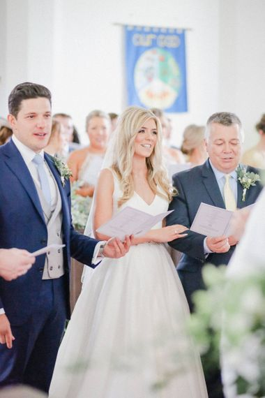 Bride and groom at the church altar singing hymns