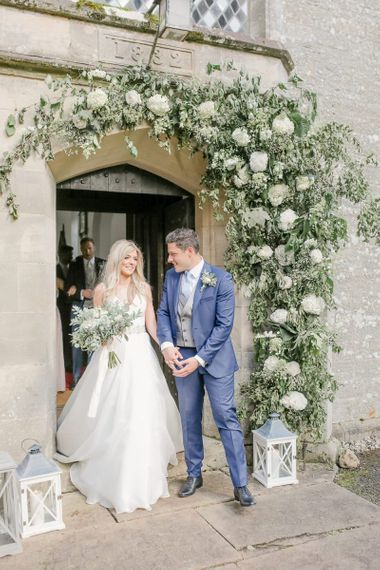 Bride in Sassi Holford wedding dress and groom in classic suit exiting the church