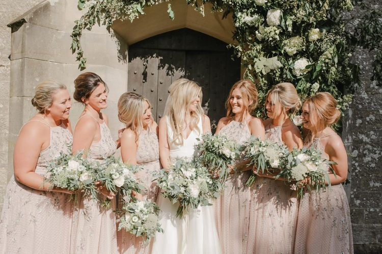 Bridal party portrait outside the church under a floral arch