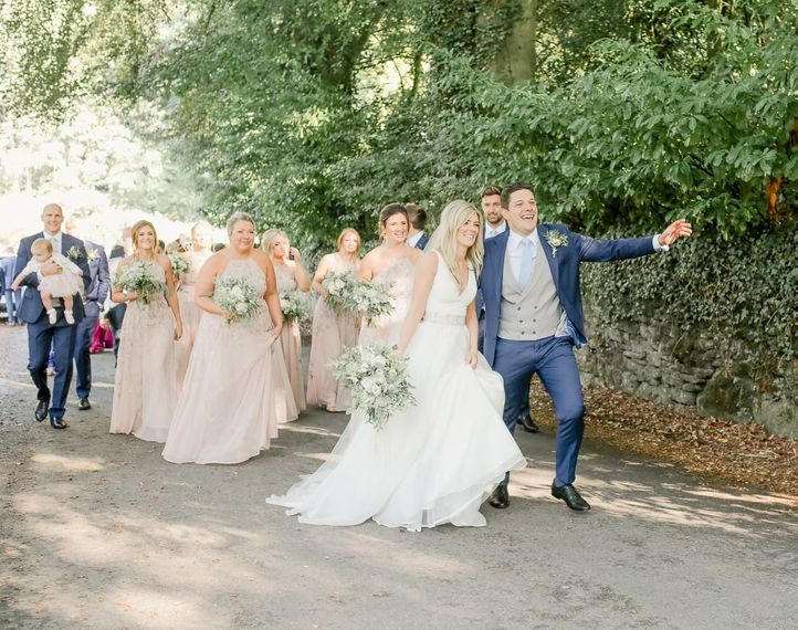 Wedding guests walking from the church to the Askham Hall  reception