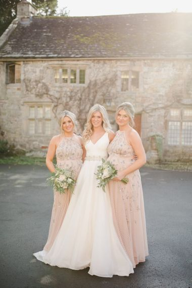 Bride in Sassi Holford wedding Dress and bridesmaids in halter neck dresses
