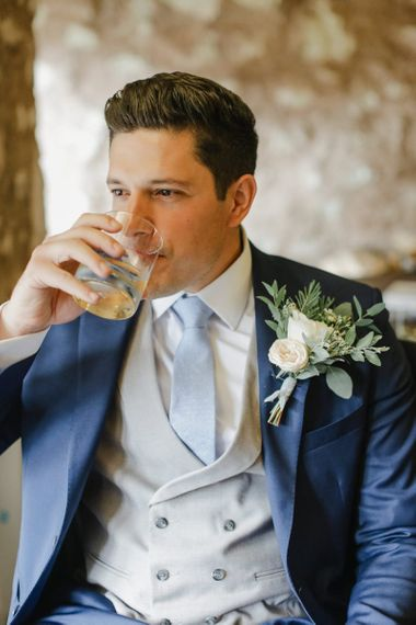 Groom in classic navy suit with grey horseshoe waistcoat
