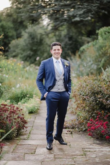 Groom in Navy suit with grey waistcoat standing in aAskham Hall  gardens