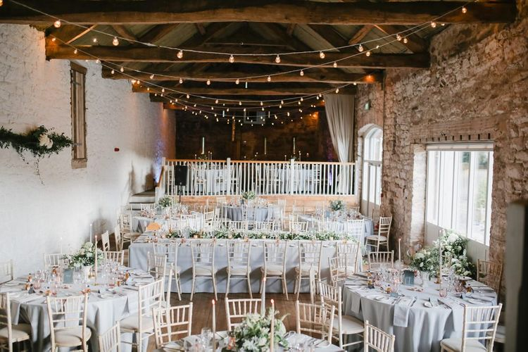 Askham Hall wedding reception with fairy lights, taper candles and foliage