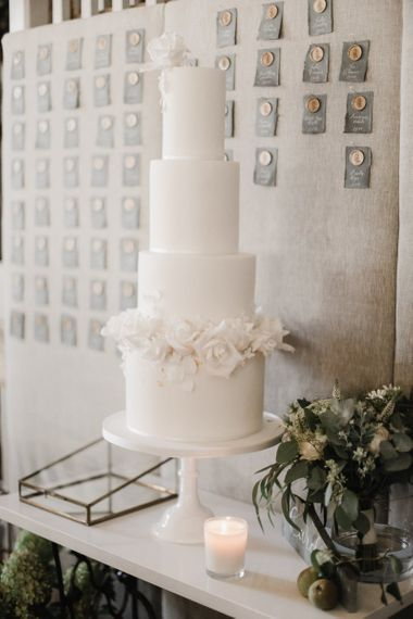 Elegant white wedding cake with wax seal escort card backdrop