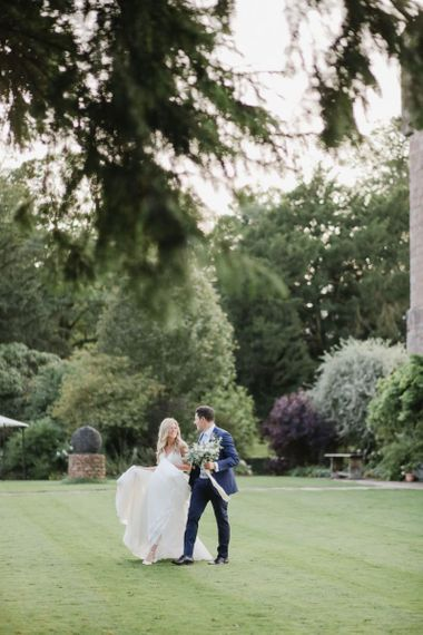 Bride and groom walking through Askham Hall gardens