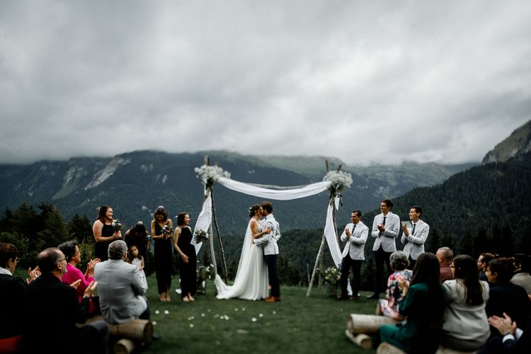 Bride in Mariées Passion Wedding Dress and Groom in Grey Blazer  Kissing at Their French Alp Wedding