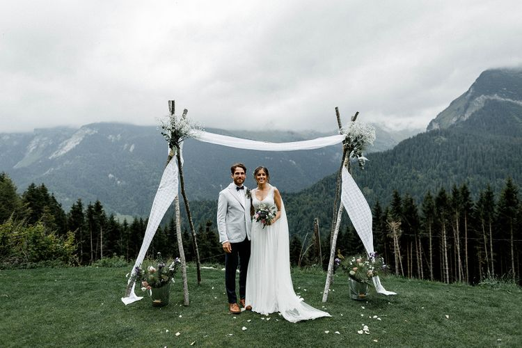 Bride in Mariées Passion Wedding Dress and Groom in Grey Blazer  Standing in Front of Their Draped Wedding Altar