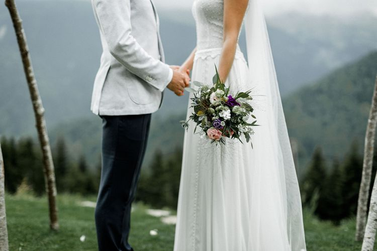 Bride in Mariées Passion Wedding Dress with Pretty Bouquet and Groom in Grey Blazer Holding Hands