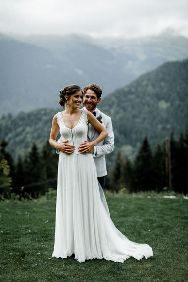 Bride in Mariées Passion Wedding Dress and Groom in Grey Blazer Embracing