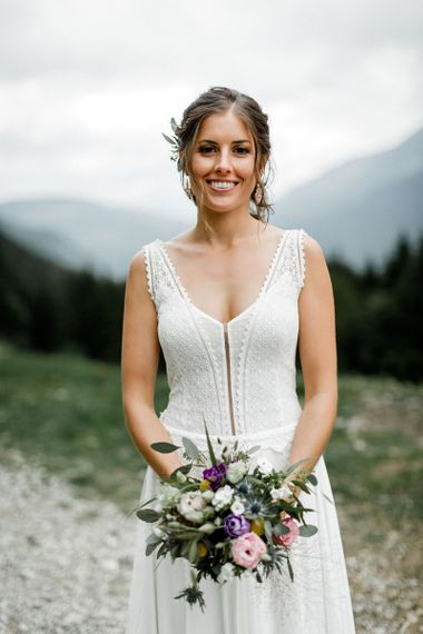 Bride in Mariées Passion Wedding Dress with  Purple, Pink, White and Green Wedding Bouquet