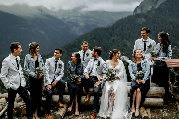 Wedding Party Picture in the French Alps with Bride in Mariées Passion Wedding Dress, Bridesmaids in Navy Dresses and Denim Jackets and Groomsmen in Grey Blazers and Navy Chinos