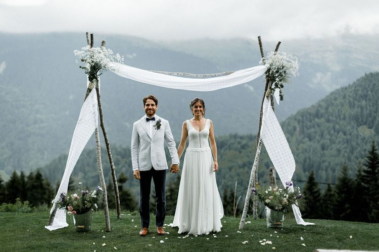 Bride in Mariées Passion Wedding Dress and Groom in Grey Blazer and Navy Chinos Standing in Front of Draped Altar