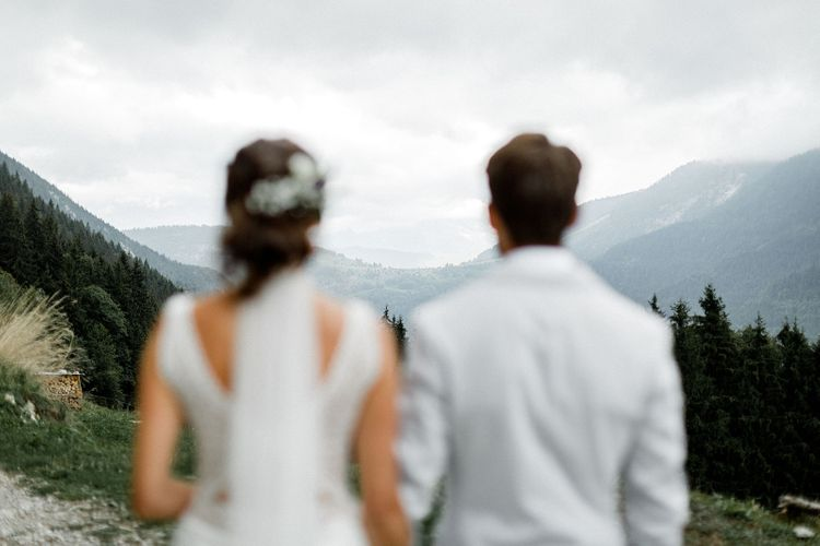 Bride in Mariées Passion Wedding Dress and Groom in Grey Blazer and Navy Chinos  Standing on the French Alps
